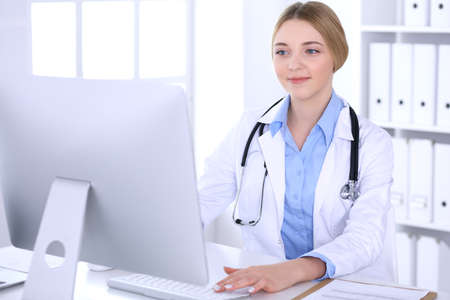 Photo for Young woman doctor at work in hospital looking at desktop pc monitor. Physician controls medication history records and exam results. Medicine and healthcare concept - Royalty Free Image