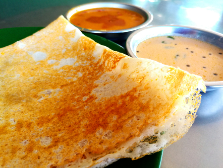 Photo for Thosai or tosai is a food of Indian society. Its mix of soft and crispy textures and tangy tones, tosai goes so well with the fresh flavors of chutney or the spicy tastes of curry. - Royalty Free Image