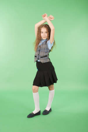 Photo pour Beautiful young girl in school uniform isolated on green background - image libre de droit