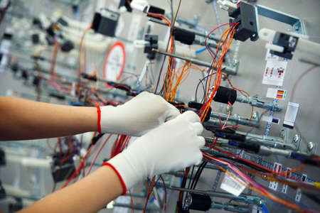 Photo pour Hands employee that manufacture the wiring for the car - image libre de droit