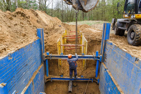 Photo pour Installation of metal supports to protect the walls of the trench. The lining protects the walls from collapsing and save the workers. - image libre de droit