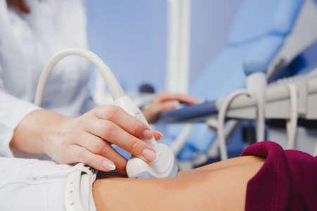 Foto de female doctor operating ultrasound scanner examining belly of her female patient - Imagen libre de derechos