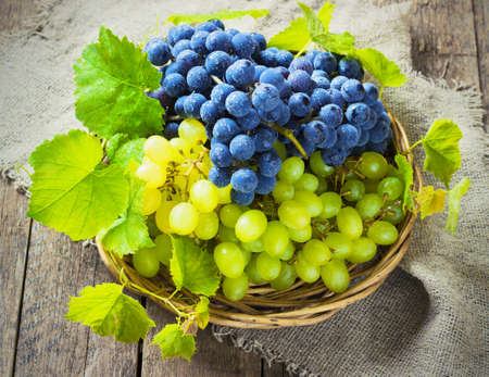 Photo for blue and green grapes in a basket on a wooden background toning - Royalty Free Image
