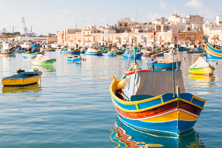 Photo pour Colorful typical boats - Mediterranean traditional fisherman village in the south east of Malta. Early winter morning in Marsaxlokk, Malta. - image libre de droit