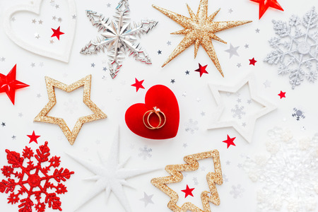 Photo for Christmas and New Year holiday background with decorations and wedding rings on gift heart box. Top view, flat lay. - Royalty Free Image