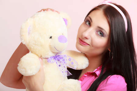 Portrait of childish young woman with headband holding toy. Infantile girl hugging teddy bear on pink. Longing for childhood. Studio shot.