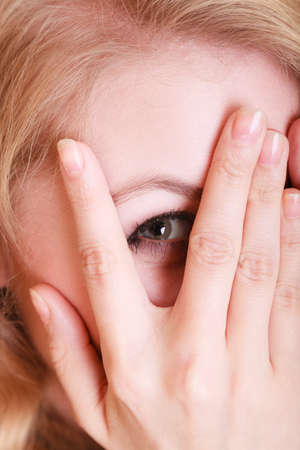 Closeup of afraid frightened woman peeking through her fingers. Shy girl covering face with hands.