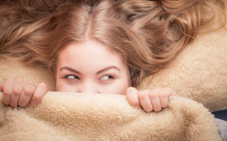 Photo pour Wake up. Lovely young woman waking up happily after good night sleep, smiling girl in the morning in bed covering her face under blanket - image libre de droit
