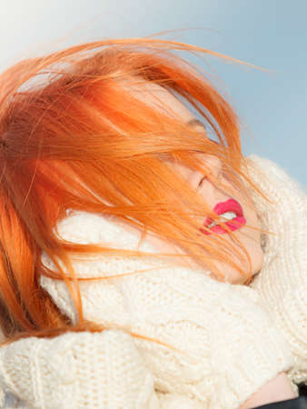 Winter fashion. Beauty redhaired head with hair blowing on wind, woman in warm clothing outdoor enjoying sunlight.