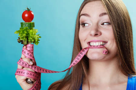 Dieting weight loss concept. Sporty girl fitness woman holding fork with fresh mixed vegetables and measuring tape on blue background