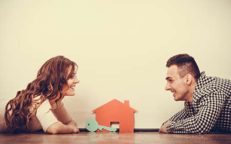 Photo for real estate, family and couple concept - smiling couple lying on floor with symbol house and key daydreaming at home, vintage filter - Royalty Free Image