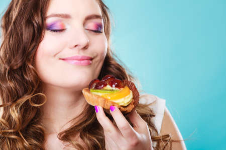 Foto de Bakery sweet food and people concept. Content attractive woman closed eyes holds cake cupcake in hand smelling blue background - Imagen libre de derechos