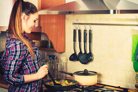 Woman in kitchen cooking stir fry frozen vegetables. Girl frying making delicious risotto. Dinner food meal.