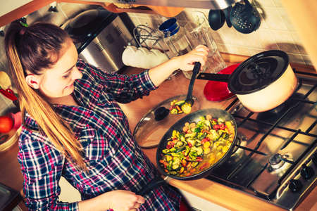 Woman in kitchen cooking stir fry frozen vegetables. Girl frying making delicious dinner food meal.