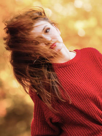 Fall lifestyle concept, harmony freedom. Beauty woman portrait with hair blowing on wind, fashion girl relaxing in autumnal park, outdoor