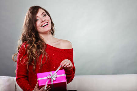 Photo for People celebrating xmas love and happiness concept - beauty girl opening present pink gift box sitting on sofa at home - Royalty Free Image
