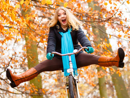 Foto de Fall active lifestyle concept. Happy crazy woman girl vivid color shawl relaxing in autumn park riding bicycle with her legs in the air having fun - Imagen libre de derechos