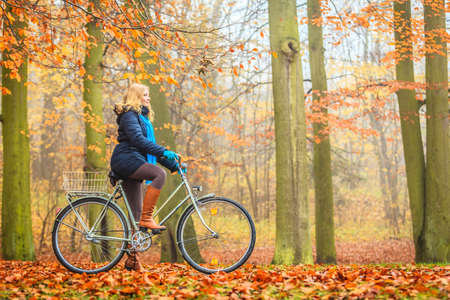 Photo for Happy active woman riding bike bicycle in fall autumn park. Glad young girl in jacket and scarf relaxing. Healthy lifestyle and recreation leisure activity. - Royalty Free Image