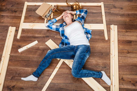 Photo pour Happy woman having fun assembling furniture at home. Young girl laying on floor arranging apartment house interior. DIY. High angle view. - image libre de droit