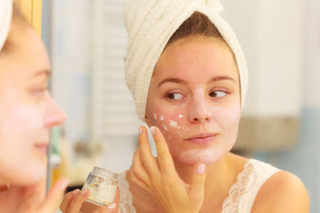 Photo pour Woman applying mask moisturizing skin cream on face looking in bathroom mirror. Girl taking care of her complexion layering moisturizer. Skincare spa treatment. - image libre de droit