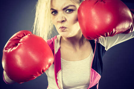 Sporty angry determined woman wearing red boxing gloves, fighting. Studio shot on dark background.