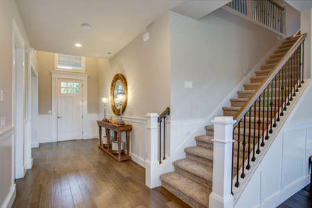 Foto de Fabulous foyer features staircase wall adorned with board and batten and fitted with a wood console table illuminated by iron buffet lamps. - Imagen libre de derechos