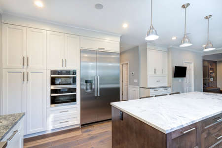 Foto de Luxury home interior boasts amazing white kitchen with custom white shaker cabinets, endless marble topped kitchen island and stainless steel appliances over wide planked hardwood floor. - Imagen libre de derechos