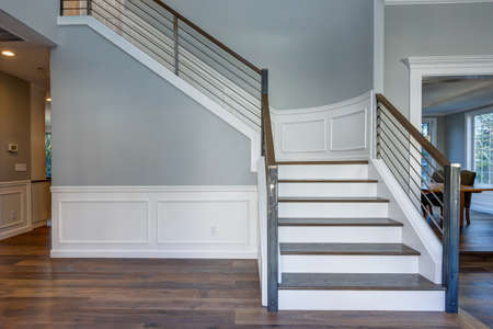 Photo pour Luxury custom built home interior. Stunning two story entrance foyer design with white wainscoting, grey walls and a white staircase.   - image libre de droit