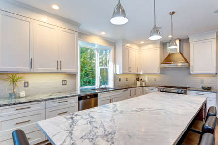 Photo pour Luxury home interior boasts amazing white kitchen with custom white shaker cabinets, endless marble topped kitchen island and stainless steel appliances over wide planked hardwood floor. - image libre de droit