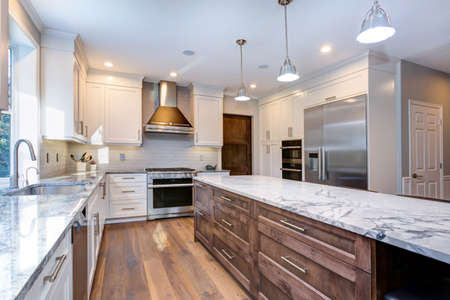 Photo pour Luxury home interior boasts amazing white kitchen with custom white shaker cabinets, endless marble topped kitchen island with drawers and stainless steel appliances over wide planked hardwood floor. - image libre de droit
