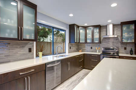 Photo for Updated contemporary kitchen room interior with white counters and dark wood cabinets fitted with luxury stainless steel appliances.  - Royalty Free Image