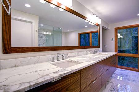 Foto de Sleek bathroom features double bathroom cabinet vanity with white gray marble countertop and white rectangle undermount sinks atop marble floor   - Imagen libre de derechos