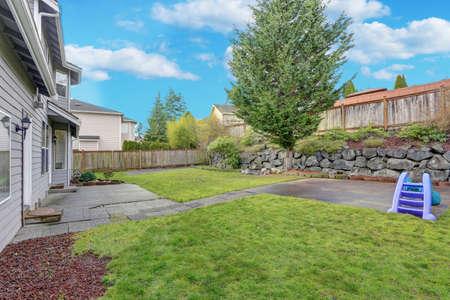 Foto de Backyard view with natural stone lanscape design and well kept lawn. - Imagen libre de derechos