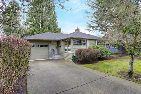 Photo for Small grey home exterior with a garage. - Royalty Free Image