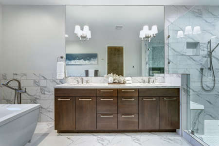 Photo for Incredible master bathroom with Carrara marble tile surround, modern glass walk in shower, espresso dual vanity cabinet and a freestanding bathtub.   - Royalty Free Image