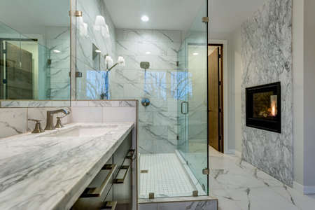 Foto de Incredible master bathroom with fireplace, Carrara marble tile surround, modern glass walk in shower, espresso dual vanity cabinet and a freestanding bathtub.   - Imagen libre de derechos