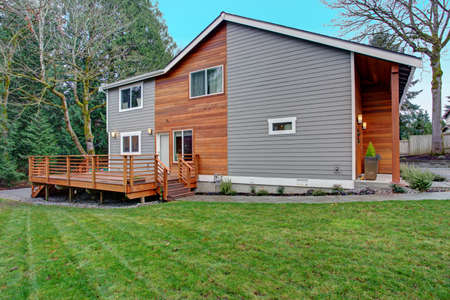 Foto de Charming newly renovated home exterior, natural wood siding and grey siding create a beautiful curb appeal. View of a nice walk out deck with wooden handrails. - Imagen libre de derechos