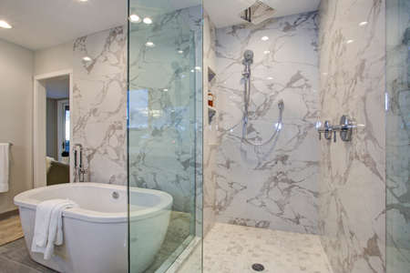 Photo for White and gray calcutta marble bathroom design with custom soaking tub and glass walk in shower. - Royalty Free Image