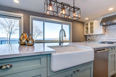 Photo pour Beautiful kitchen room with green island and farmhouse sink. - image libre de droit