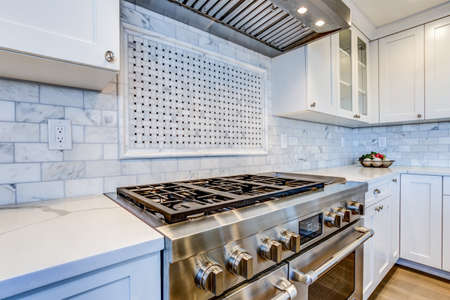 Photo pour White Kitchen with stainless steel hood over gas cooktop and carrera marble backsplash. - image libre de droit