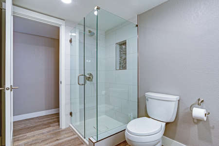 Photo pour Elegant bathroom with glass shower and hardwood floor. - image libre de droit