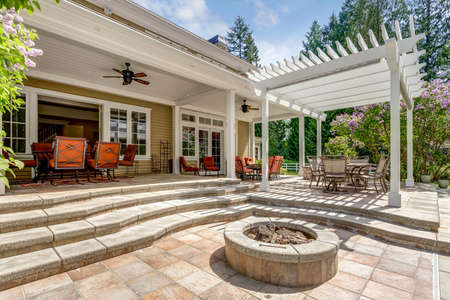 Photo for Lovely outdoor deck patio space with white pergola, fire pit in the backyard of a luxury house. - Royalty Free Image