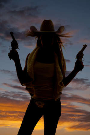 Photo for A silhouette of a cowgirl pointing her pistols up in the sky. - Royalty Free Image