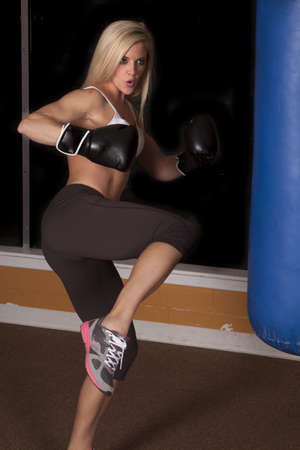 a woman getting ready to kick the bag with her foot.