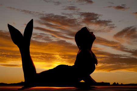 Foto de A silhouette of a mermaid in the sunset. - Imagen libre de derechos