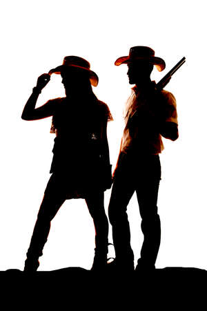 Photo for a silhouette of a cowgirl and a cowboy.  He is holding onto a gun. - Royalty Free Image