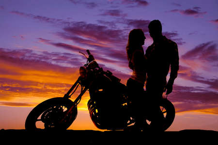 Photo for A silhouette of a man and woman next to a motorcycle in the outdoors. - Royalty Free Image