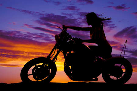Photo for A silhouette of a woman on a motorcycle sitting with the wind blowing through her hair. - Royalty Free Image