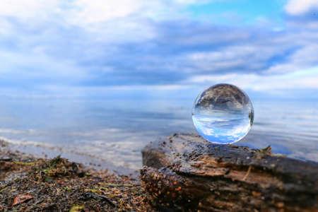 Photo pour Transparent glass ball on a log reflecting calm blue water of a lake - image libre de droit