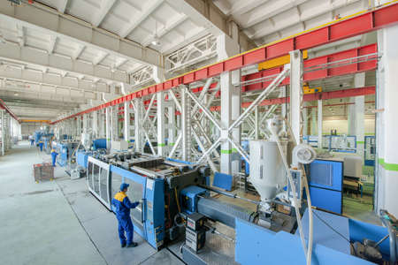 Photo for Industrial injection molding press machine for the manufacture of plastic parts using polymers in the management of worker - Royalty Free Image